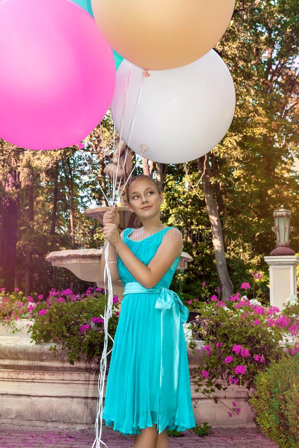 Pretty young girl with big colorful balloons walking in the park near the town - image stock photo