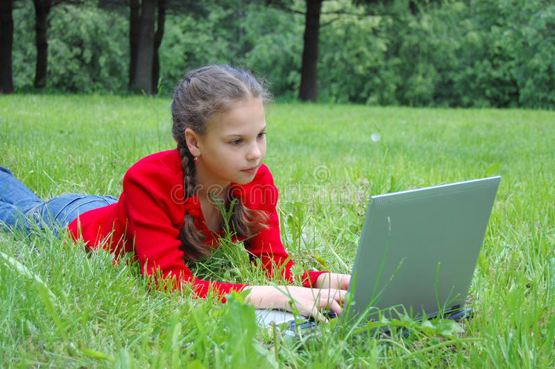 Pretty young girl with a modern laptop stock photos