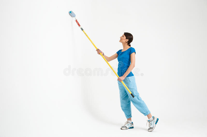 Pretty young girl painting the wall with roller. stock photo