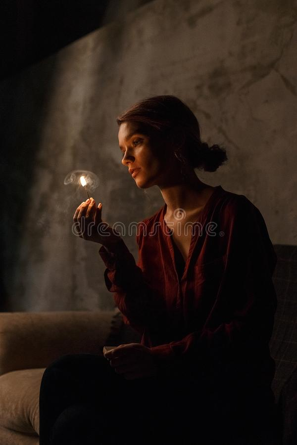 Pretty young girl in red shirt sits in dark gloomy room, looks thoughtfully at fire of burning match and holds matchbox stock photography