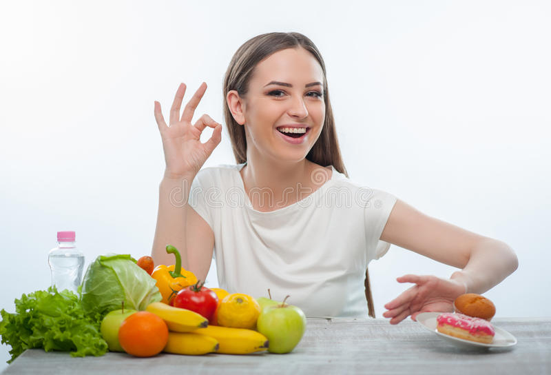Pretty young girl is refusing to eat unhealthy. Beautiful woman is pushing the plate with donuts aside. She decided to eat only healthy vegetables and fruits royalty free stock images
