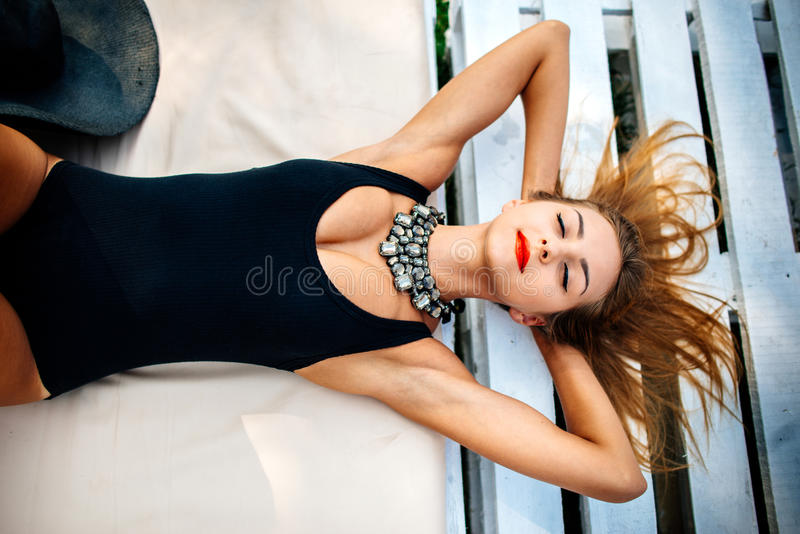 Pretty young girl relaxing outdoor in black swimwear. Young pretty girl relaxing outdoor in black swimwear royalty free stock image