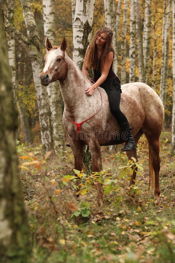Pretty young girl riding a horse without any equipment in autumn stock photos