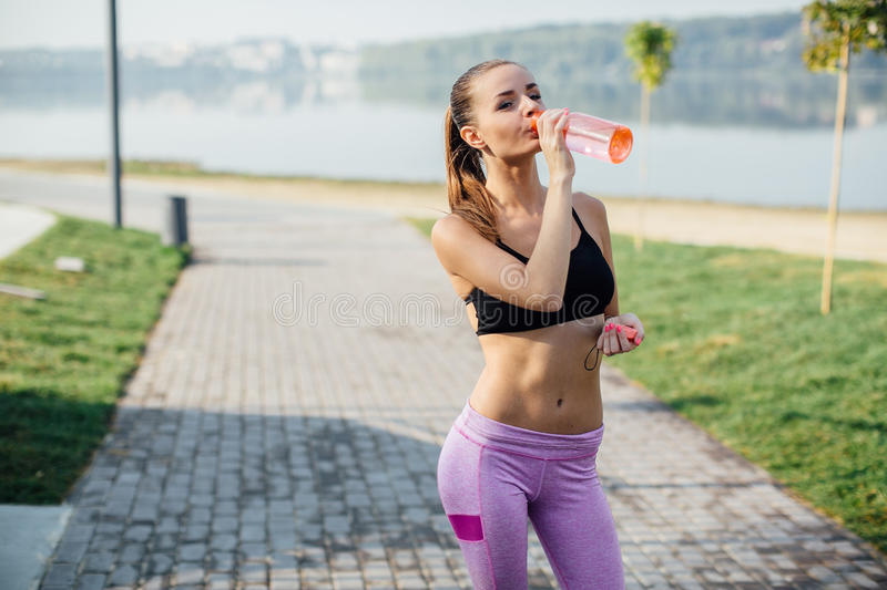 Pretty young girl running in the park and drinking water royalty free stock photo