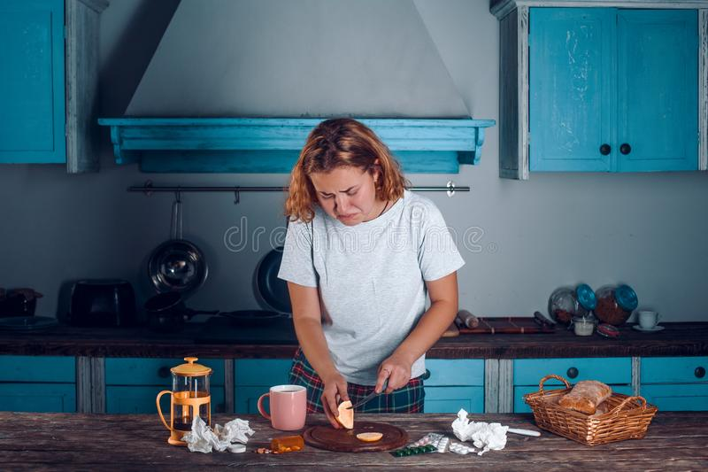Concentrated woman slices lemon on cutting board in the kitchen. stock photos