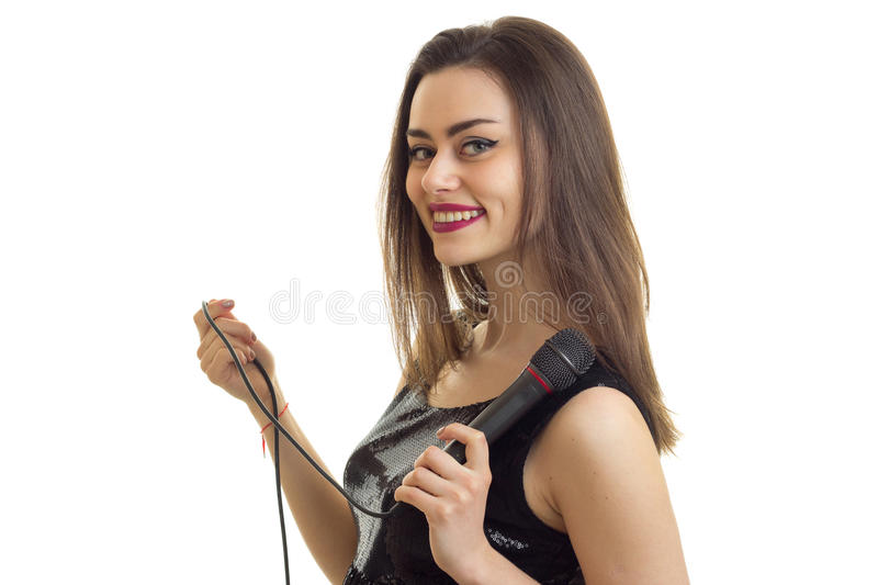 Pretty young girl smiles and sings karaoke and smiles stock images