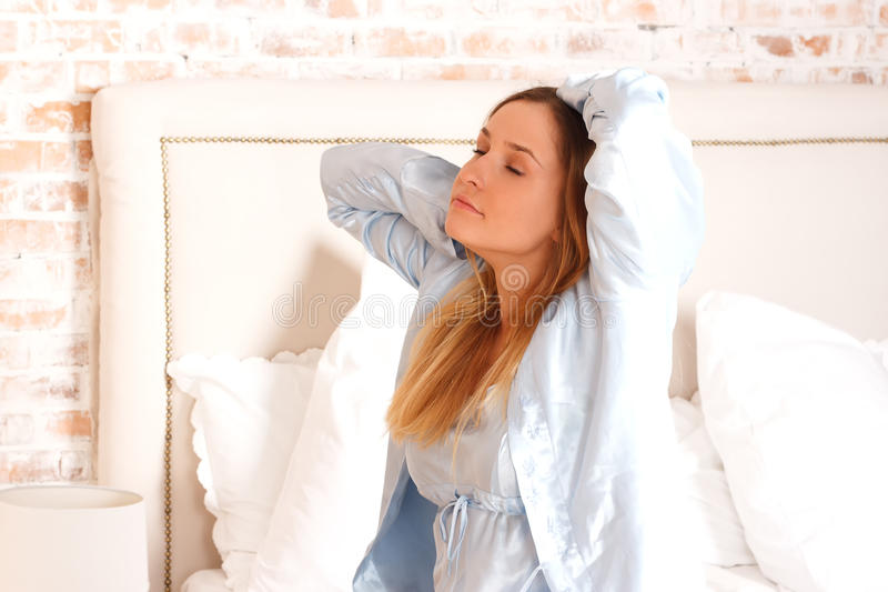 Pretty young girl stretches in bed royalty free stock photography