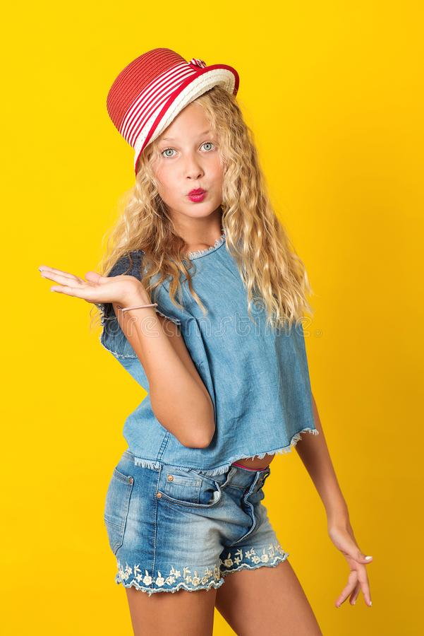 Pretty young girl in summer hat over yellow background. Cute girl sending kiss. Summer fashion. Happy girl, denim style stock photos