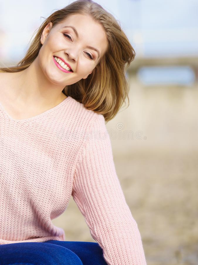Woman in sweater walking on beach royalty free stock photography