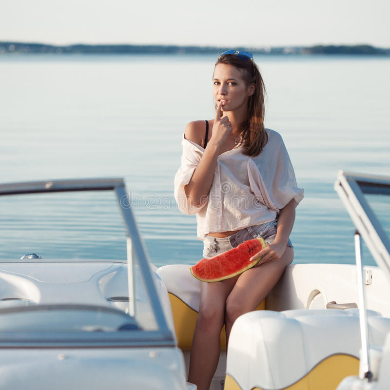 Pretty young girl with watermelon posing on a yacht royalty free stock photography