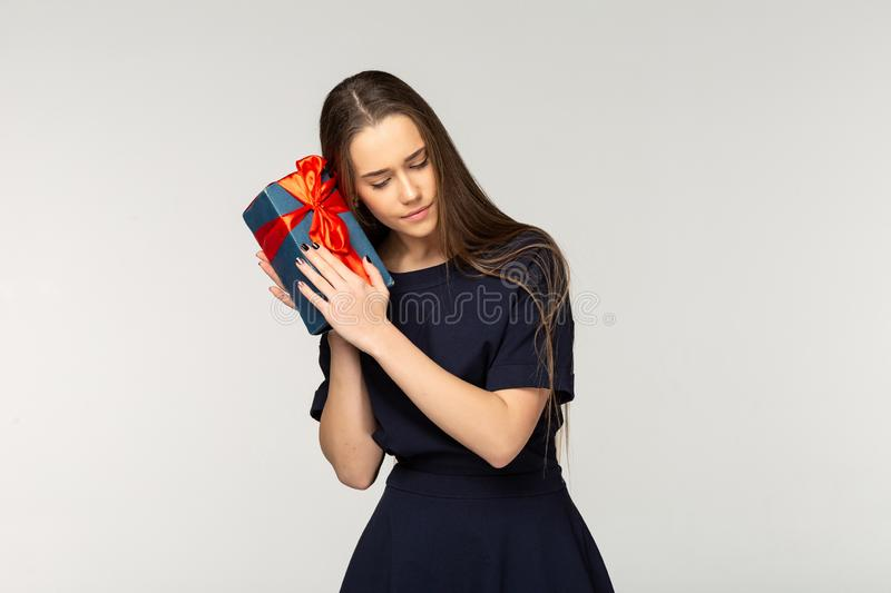 Pretty young girl wearing dark dress holding gift box royalty free stock photography