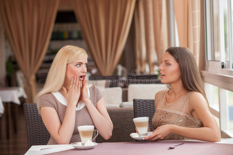 Pretty young girls are gossiping in cafeteria royalty free stock photo