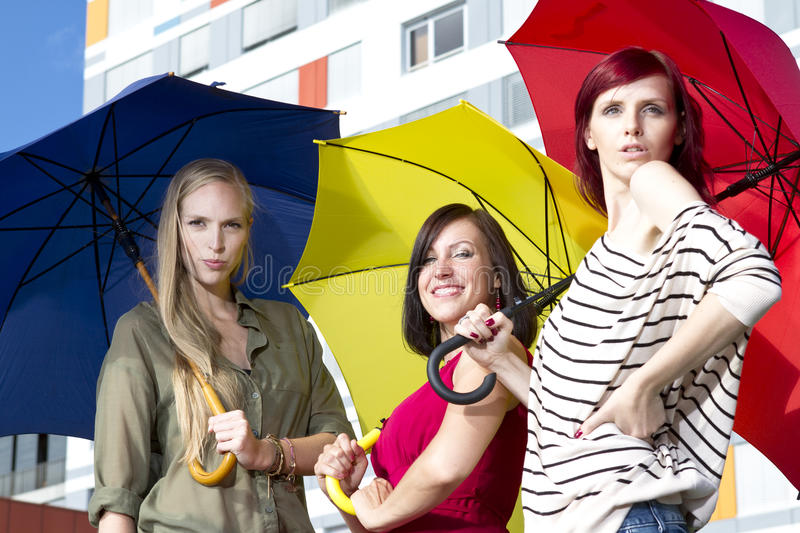Pretty young girls with umbrellas stock image