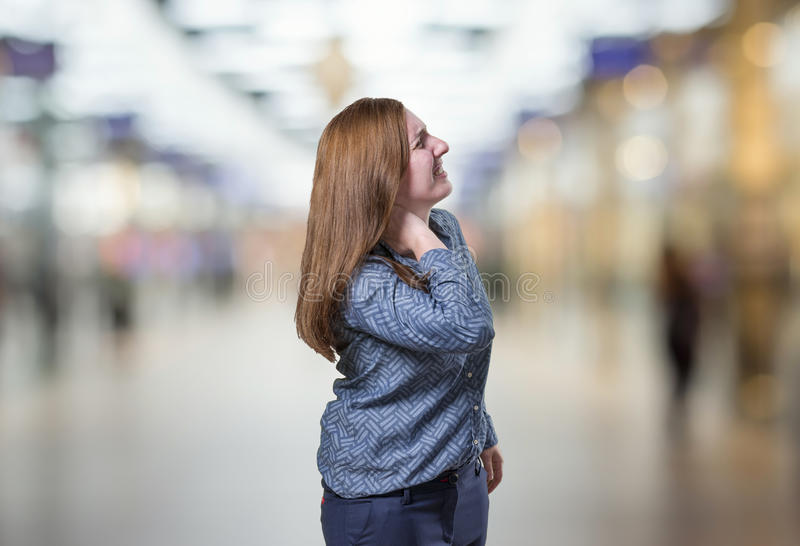 Pretty young happy business woman neck pain over blur background royalty free stock photos