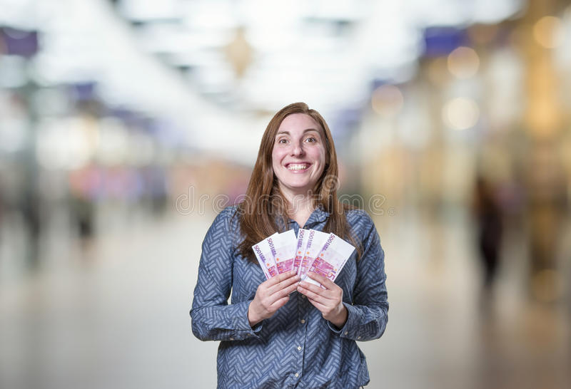 Pretty young happy business woman taking a lot of money over blu royalty free stock photos