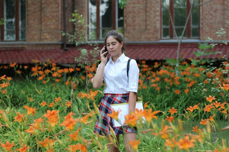 Schoolgirl girl with long hair in school uniform talking on the phone royalty free stock image