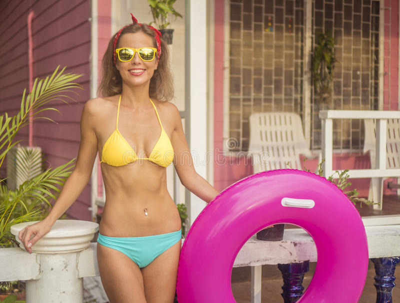 Pretty young happy woman wearing bikini and sunglasses posing with pink inflatable ring on the background of pink house.  stock photo