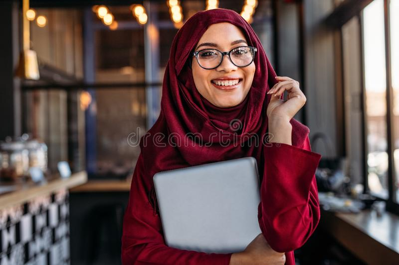 Smiling businesswoman in hijab at coffee shop stock photo