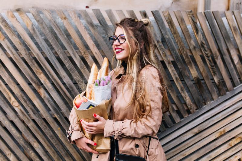 Pretty young lady with cute hairstyle and glasses returnes from grocery store walks along the street. Smiling charming. Girl with long blonde hair going home royalty free stock images