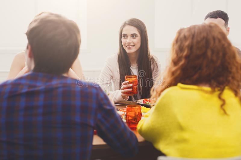 Pretty young lady at dinner table with friends stock image