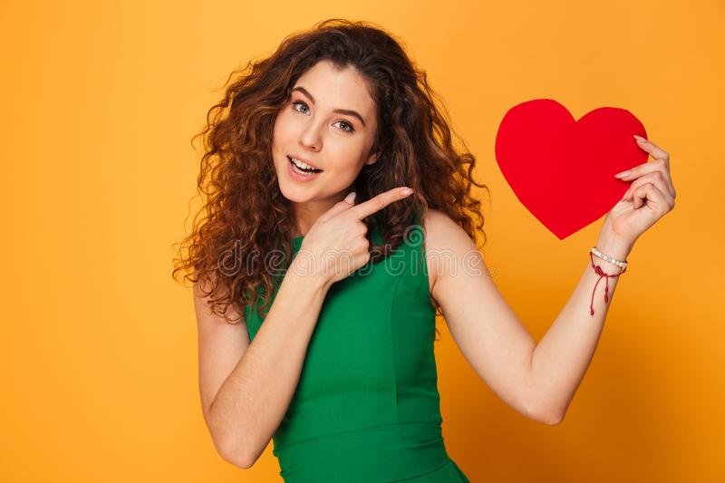 Pretty young lady holding heart pointing. royalty free stock photos