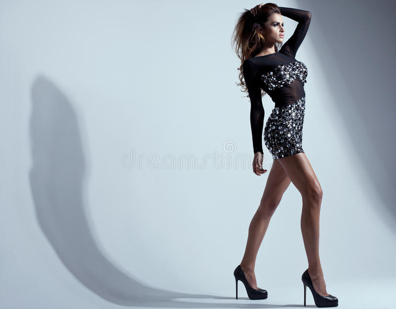 Pretty young lady. With long legs in a fashion pose royalty free stock images
