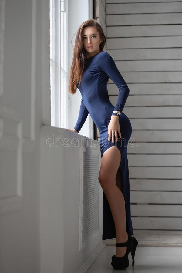 Pretty young lady. Posing against the backdrop of a wooden wall standing near the window dressed in a long blue dress royalty free stock photos