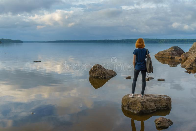 Pretty young lady with red hair standing on stone near bay shore in summer evening. Tourist on the beautiful landscape background royalty free stock photo