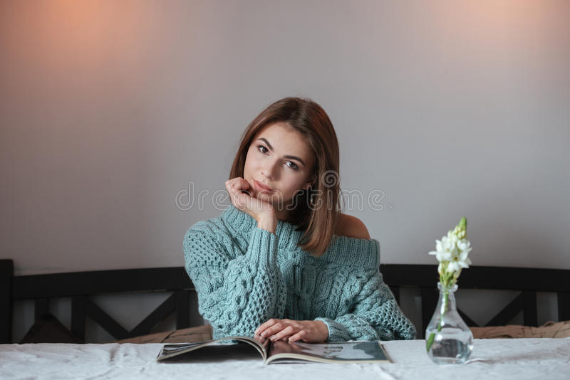 Pretty young lady sitting in cafe and reading magazine. royalty free stock photos