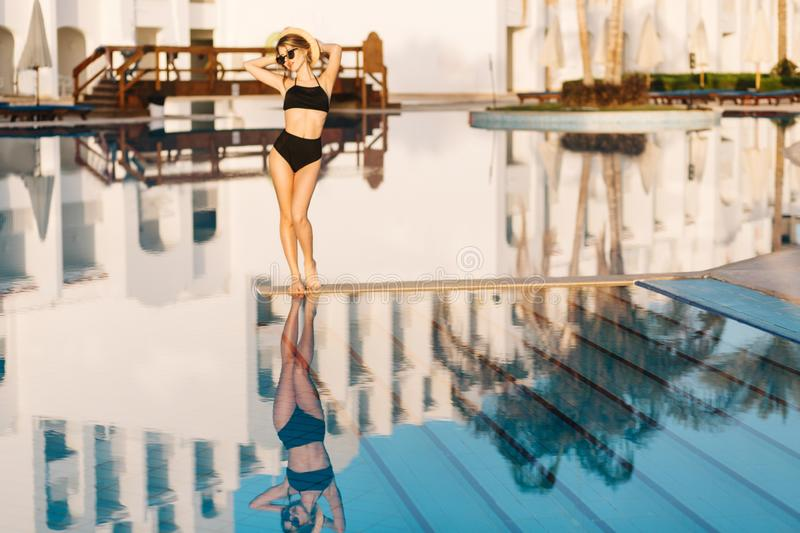 Pretty young lady, skiny girl in the midle of big nice pool near luxury resort hotel. Spending summer time, holiday, spa. Weekend. Wearing black stylish retro royalty free stock photo