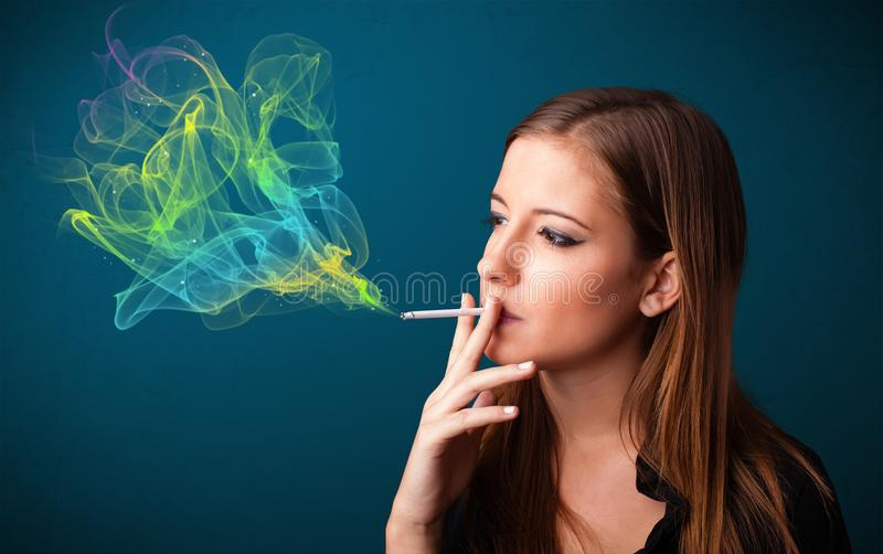 Pretty lady smoking cigarette with colorful smoke. Pretty young lady smoking cigarette with colorful smoke stock images