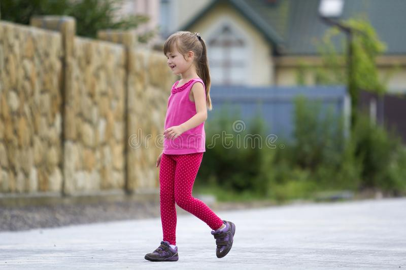 Pretty young long-haired blond child girl in pink casual summer clothing walks smiling along sunny street on blurred stone fence a royalty free stock photography