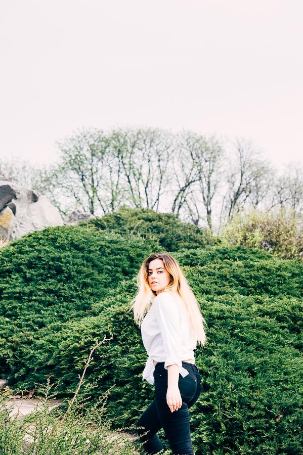 A pretty young long haired girl walking in a park stock photography