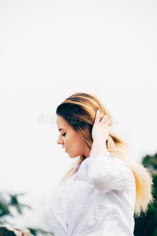 A pretty young long haired girl in white shirt royalty free stock photos
