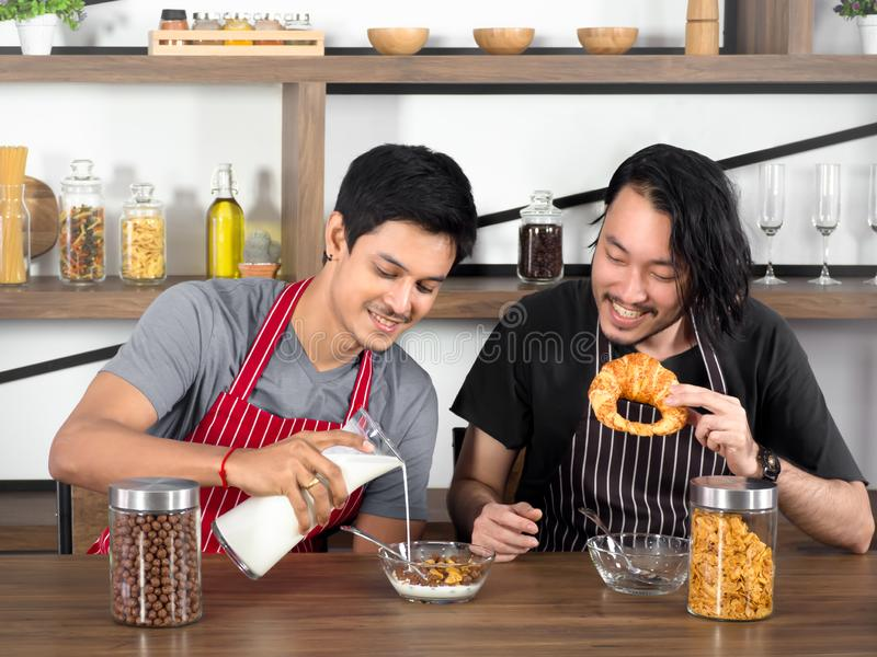 Pretty young lover having breakfast,one man pouring milk into cereal and the other holding croissants. stock photo