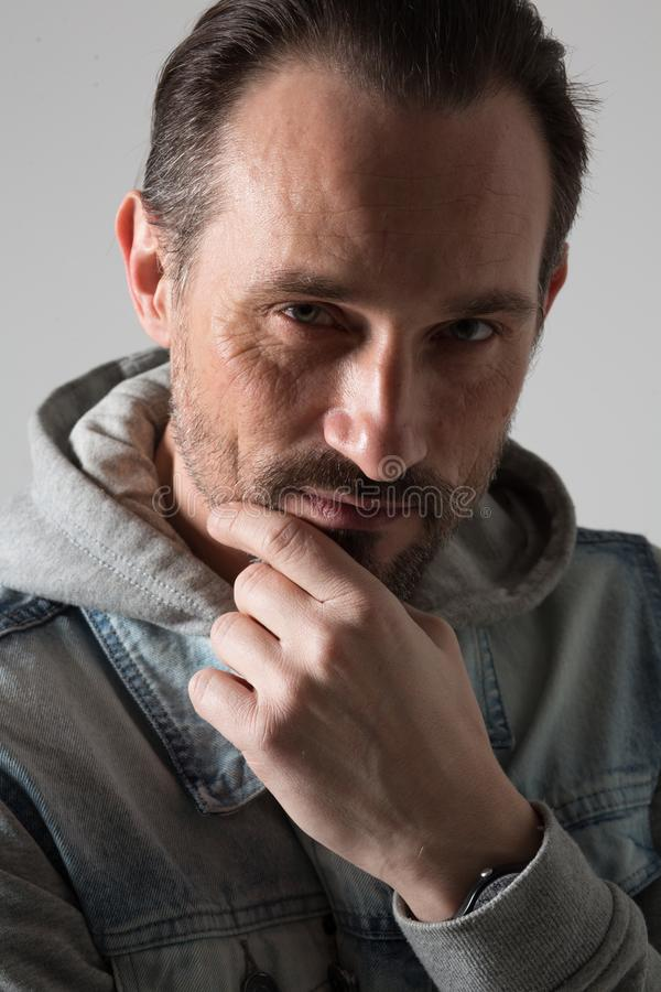Pretty young man posing. Young thoughtful male person having hand on chin. Handsome man concept royalty free stock photo