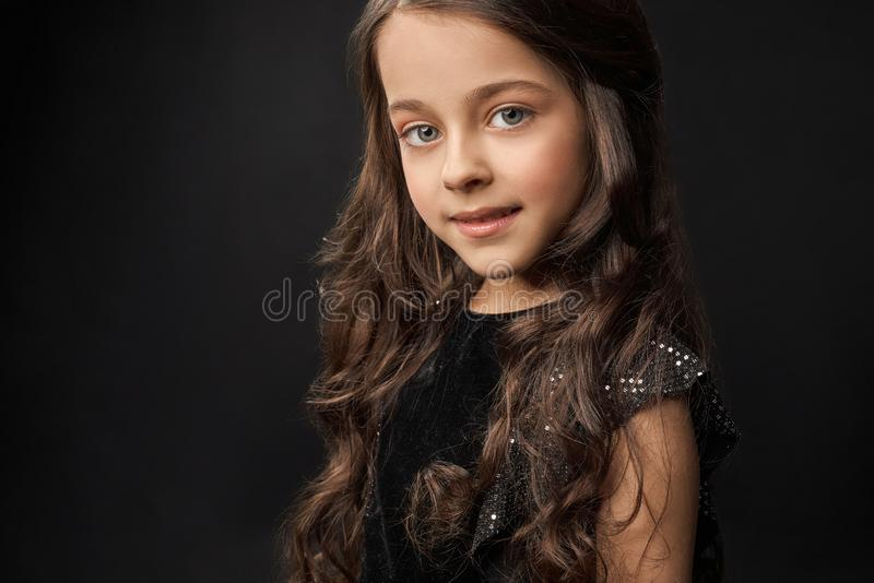 Pretty, little model with long, curly hair posing in studio. Pretty, young model in black dress with long, curly hair looking at camera. Stylish, brunette stock images