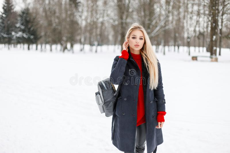 Pretty young model girl in fashion coat with a red sweater. With a stylish bag walks in the park stock photography