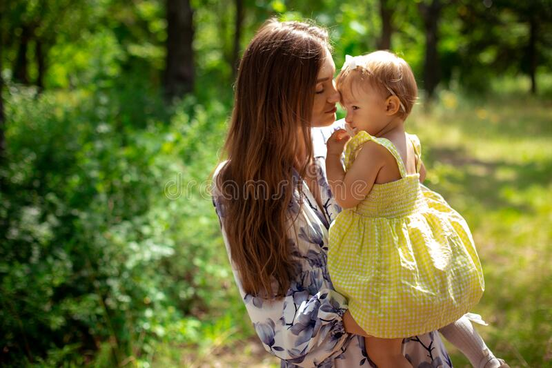 Pretty young mom having fun with her little daughter at the park stock photos