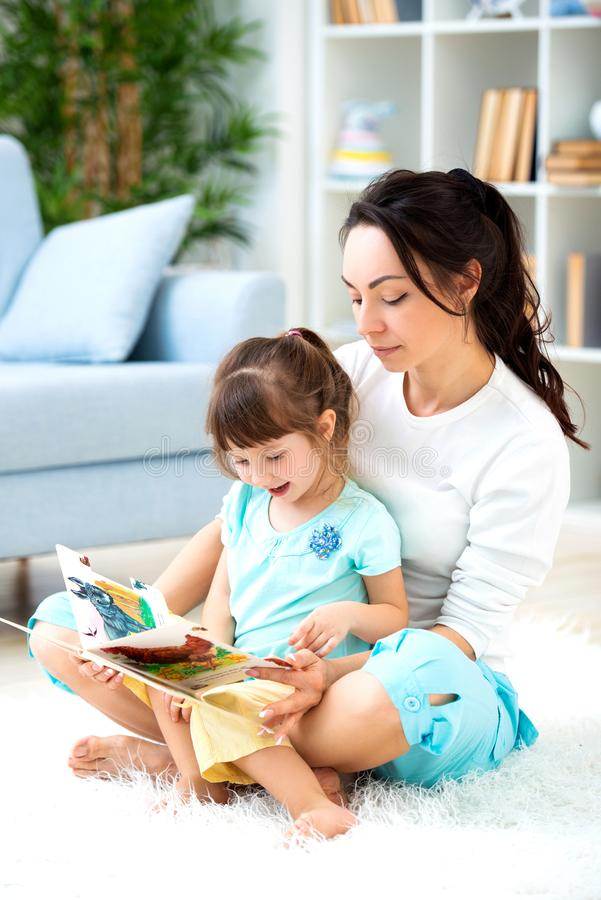 Pretty young mother reading a book to her daughter sitting on the carpet on the floor in the room. Reading with children royalty free stock image