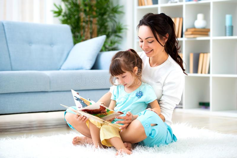 Pretty young mother reading a book to her daughter sitting on the carpet on the floor in the room. Reading with children royalty free stock photography