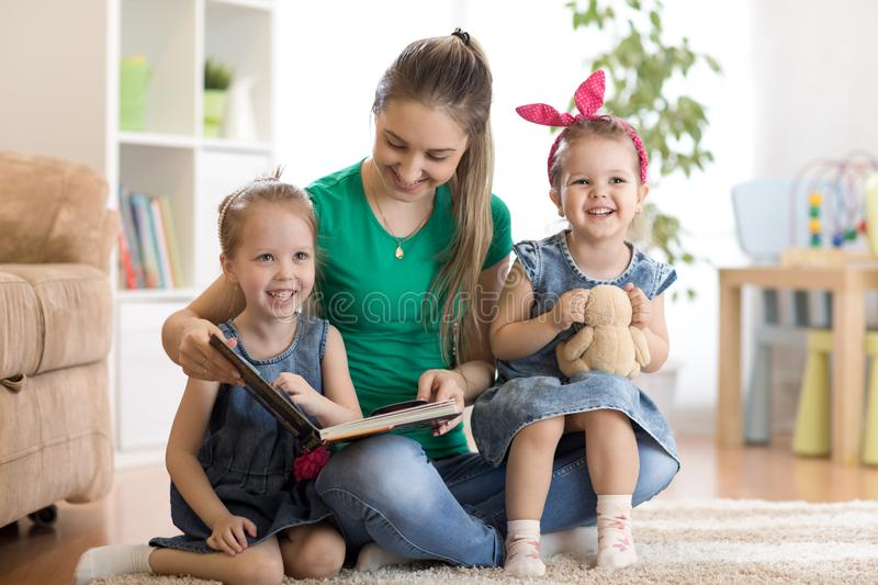 Pretty young mother reading a book to her daughters stock photos