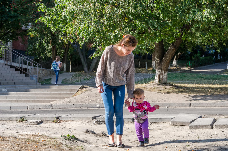 Pretty young mother walking with her daughter beautiful baby girl, and playing in the park among the trees and bushes royalty free stock photography