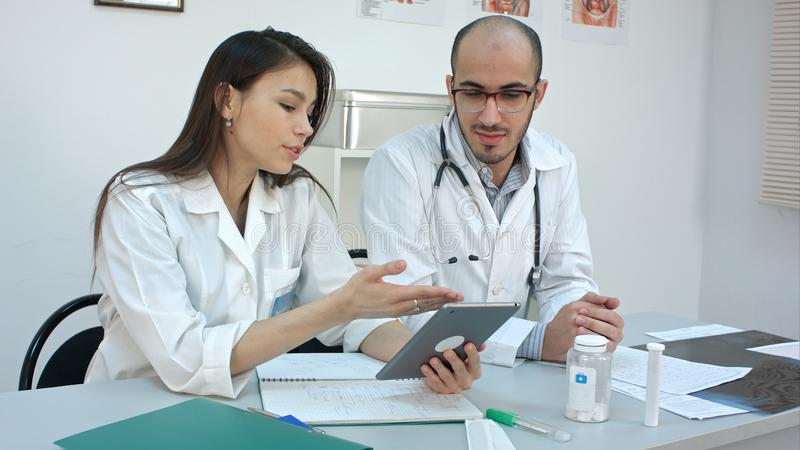 Pretty young nurse showing something on the tablet to her male colleague stock photo