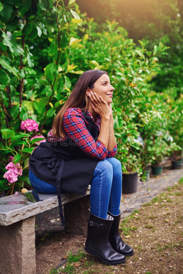 Pretty young nursery worker sitting daydreaming stock image