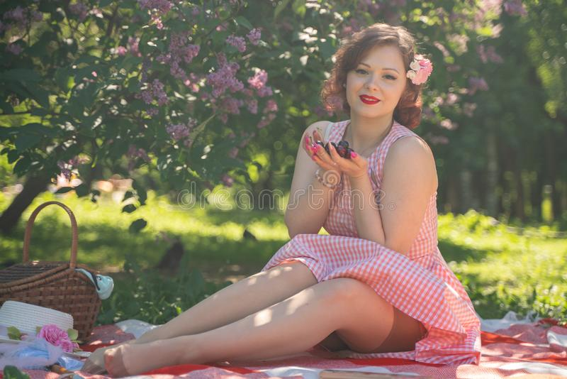 Pretty young pin up girl having rest on the nature. happy slim young woman wearing vintage dress sitting on the tartan plaid and r. Elaxing by summer day alone royalty free stock image