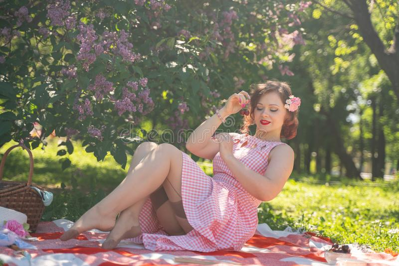 Pretty young pin up girl having rest on the nature. happy slim young woman wearing vintage dress sitting on the tartan plaid and r. Elaxing by summer day alone royalty free stock images