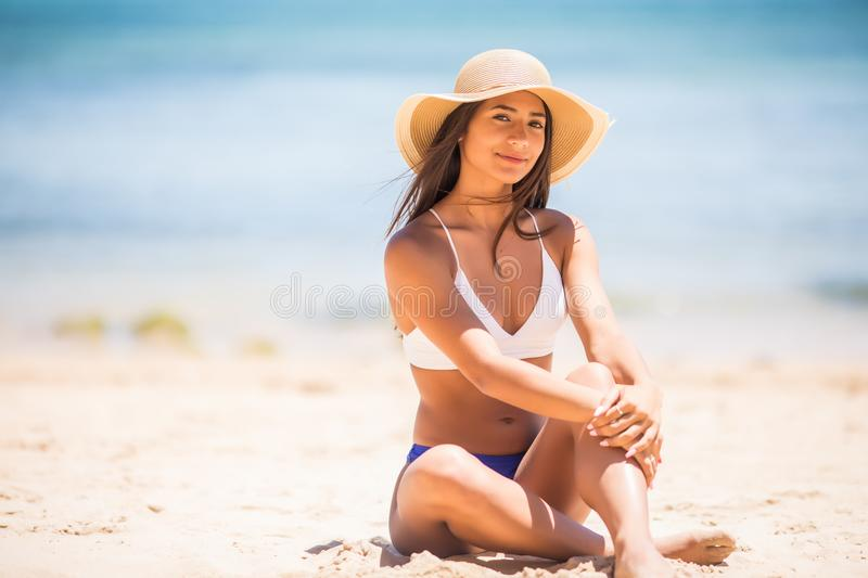 Pretty young latin pretty girl at beach. Woman sitting on sands have active time in summer playing with sand. Summertime carefree royalty free stock photography