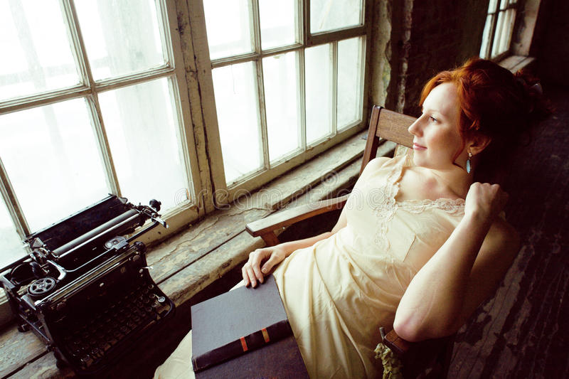 Pretty young red hair woman in old -fashioned style room sitting smiling at window and typing machine, art vintage. Hipster concept royalty free stock photography