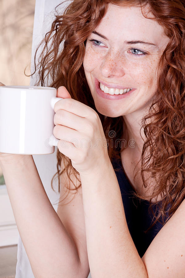 Pretty young redhead woman with freckles and coffe stock images